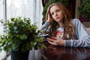 Dívka používá mobilní telefon na sociálních sítích