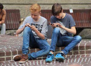 Chlapci hrají na mobilním telefonu hry